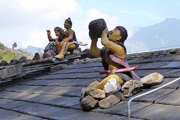 スレート屋根の上で酒を飲む男のオブジェ