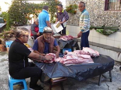 豚肉を細切れにするおじさんたち
